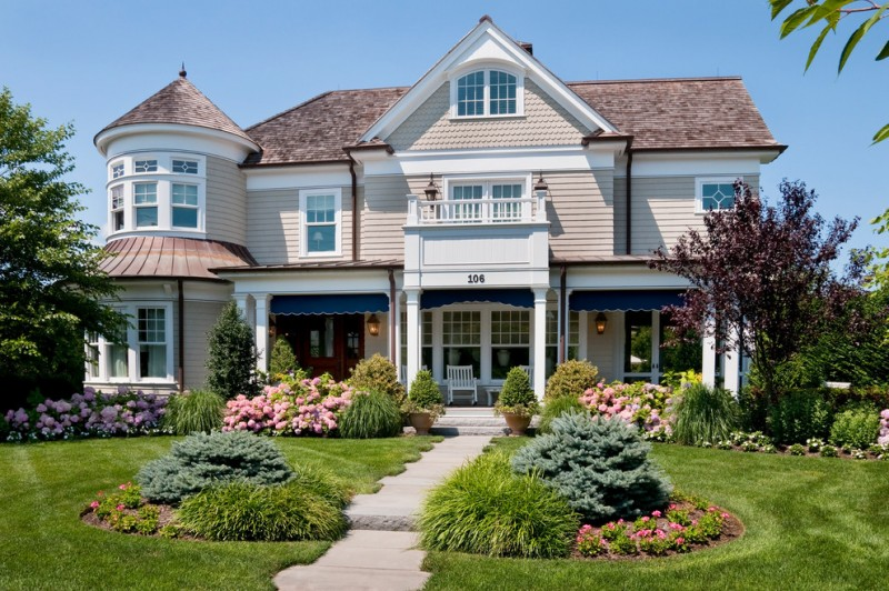 large Victorian front yard landscape with a garden path and concrete pavers hydrangeas blue spruce bushes deck wooden wall white chairs and table