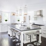 large kitchen islands with seating and storage dark floor modern chairs faucets sink chandeliers stove windows transitional kitchen
