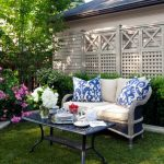 lattice fence designs cushioned bench throw pillows metal table stone pavers flowers grass patio glass vase traditional design