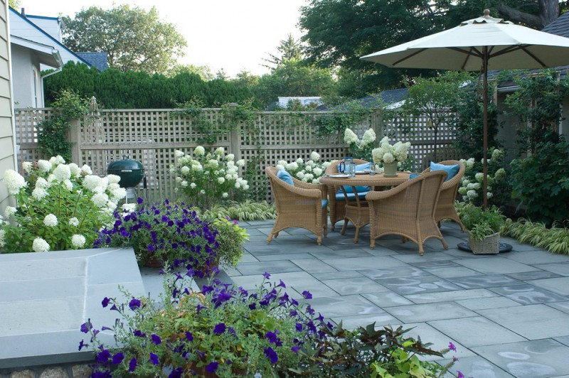lattice fence designs stone pavers sunbrella armchairs round table flowers patio traditional design