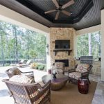 Light Toned Stone Outdoor Corner Fireplace Marble Floor Wooden Hanging Fan Cream Rug Wooden Framed Chairs Round Table
