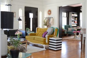 living room with bright yellow vintage sofa, white black stripped side table, black sofa, black floor lamp