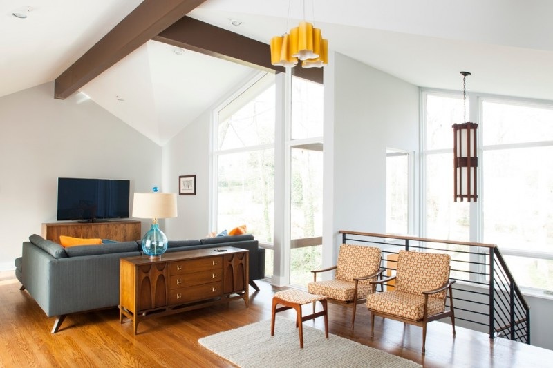 living room with mid century furniture on credenza with grey sofa with blue orange pillows, orange chairs with ottoman, orange pendant, grey rug