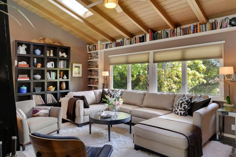 living room with sectional sofa bookshelves books cool lamps small tables carpet chairs big windows contemporary style