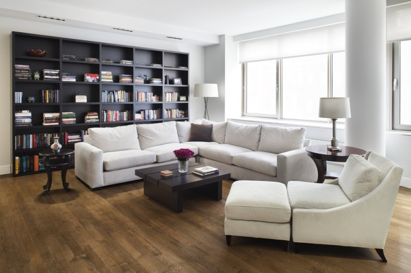living room with sectional sofa bookshelves books pillows chaise longue low table round top tables lamps windows contemporary style