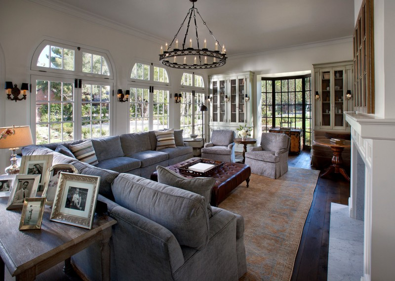 living room with sectional sofa cool lamps carpet dark floor ottoman table tables chandelier pillows traditional style