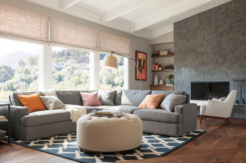 living room with sectional sofa pillows carpet ottoman painting lamp chair wood floor shelves books contemporary style