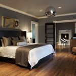 living spaces bedroom sets bed sidetables couch footrest hardwood floors grey walls ceiling lights armchairs desk fireplace double glass doors contemporary design