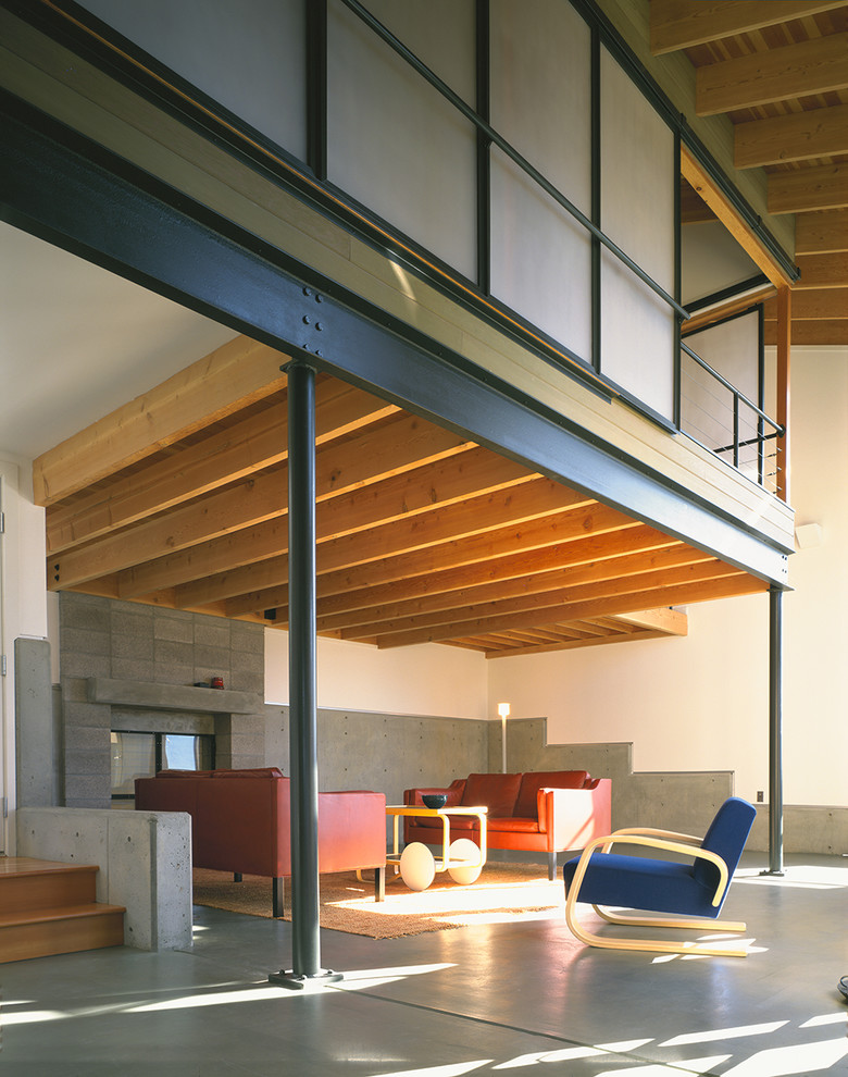 living spaces couches armchair coffee table stairs concrete floors column ceiling carpet railing modern design