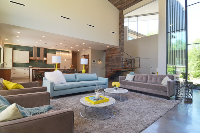 living spaces couches armchairs concrete floors coffee table carpet white cabinet wood stairs ceiling lights contemporary design