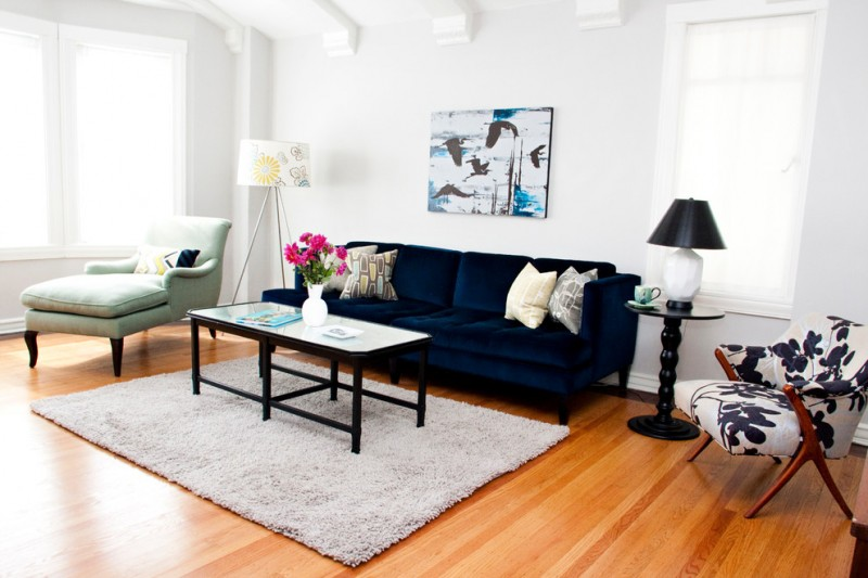 living spaces couches beautiful wood floor small tables lamps chair windows pillows flowers eclectic room