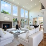 living spaces couches hardwood floor ceiling lights coffee table fireplace chairs white walls decorations transitional design