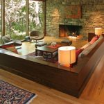living spaces couches hardwood floor textured stone wall fireplace window wall chairs coffee table carpet stool contemporary design
