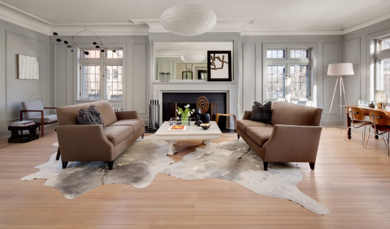 living spaces couches marble coffee table armchair cowhide rug hardwood floor standard fireplace chairs desk lamps pendant decorations sidetable