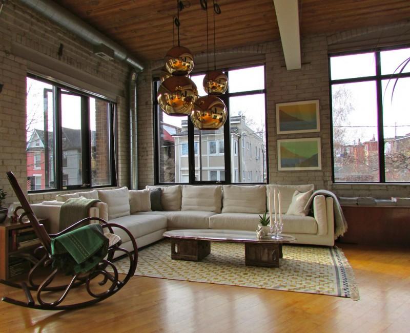 living spaces sectionals modular sofa rocking chair sidetable sideboard coffee table rug hardwood floors brick walls oversized windows decorative pendants industrial design