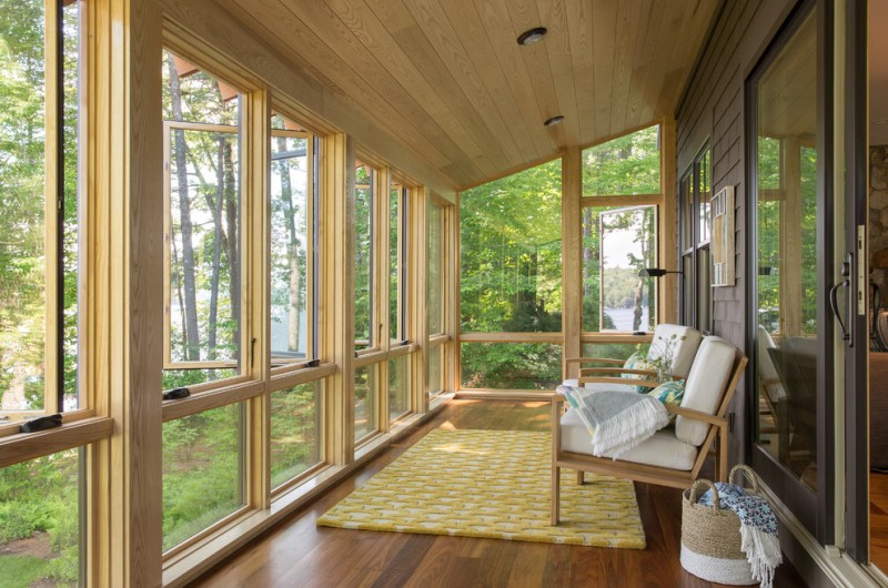 long sunroom with yellow rug, wooden sofa with white cushion