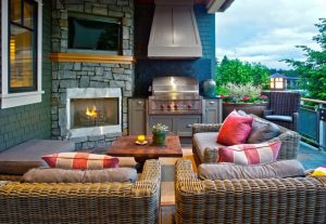 mid sized classic backyard patio design with a fire feature, a roof extension and natural stone pavers rattan framed sofa pillow throws coffee table