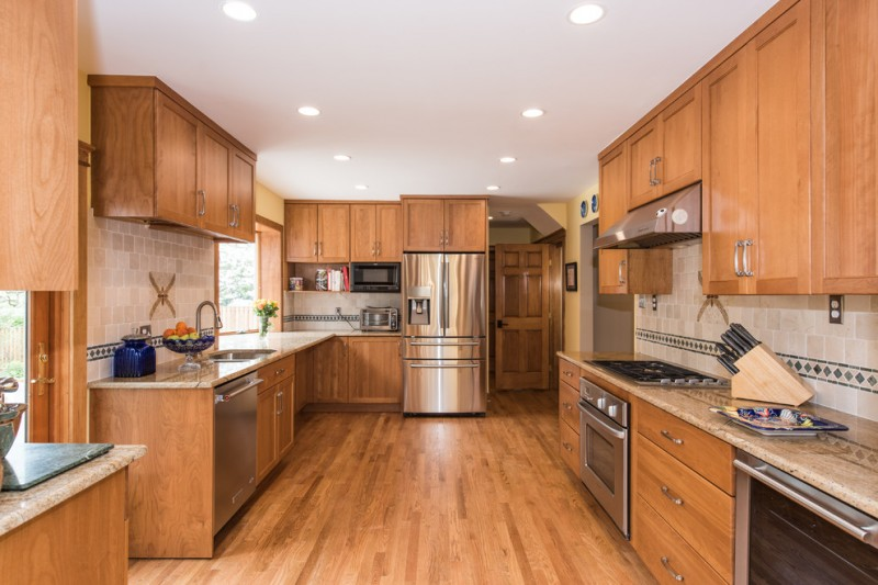 mission style U shaped kitchen design wooden cabinets granite countertop stainless steel appliances light beige tiles backsplash with diamond cut accent tiles bamboo slabs floorings