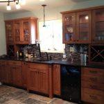 Mission Style Wet Bar Design Dark Finished Oak Cabinets Copper Undermount Sink Dark Mosaic Tiles Backsplash Dark Countertop X Door Wine Storage Shabby Tiles Flooring Idea