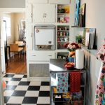 Mix Modern & Mid Century Kitchen And Dining Room With White Corner Cabinet Featuring Recessed Oven & Open Shelves Black & White Tiles Floors Movable Stainless Steel Cart