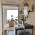 modern entryway table cube ottoman mirror wall sconces hardwood floors glass vase chair sideatable lamp traditional design