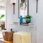 modern entryway table hardwood floors carpet framed artwork wall sconces vase books sculpture ottoman basket transitional design