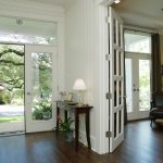 Modern Entryway Table Hardwood Floors White Walls Ceiling Lights Lamp Double Glass Doors Flower Vases Traditional Design