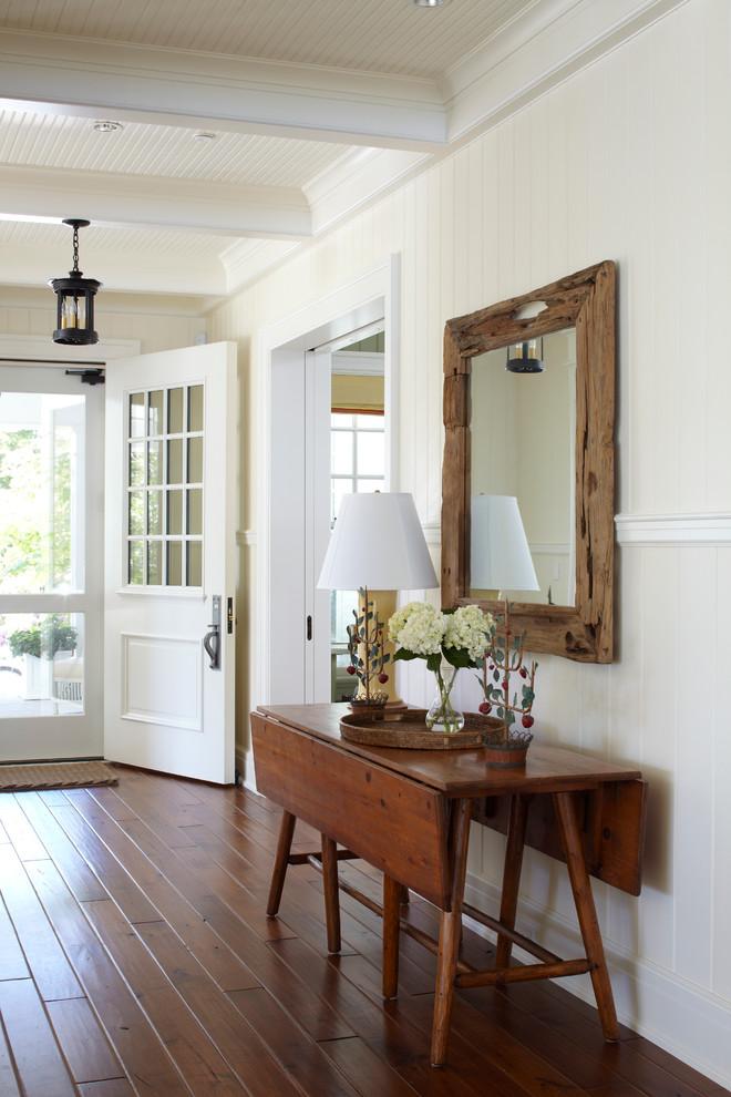 modern entryway table lamp mirror doors tray flower vase hardwood floors white walls traditional design