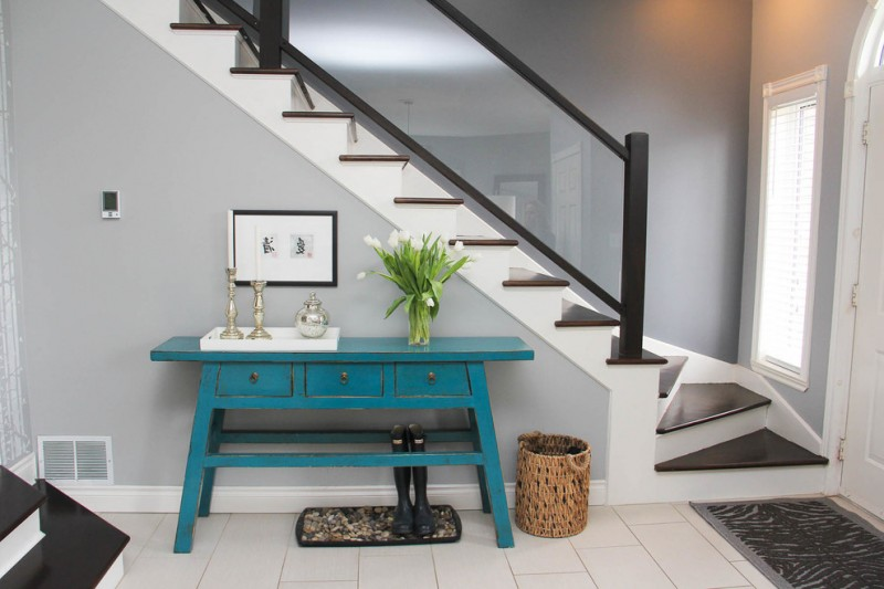 modern entryway table wood staircase white floors large window basket candleholder rug boots framed painting eclectic design