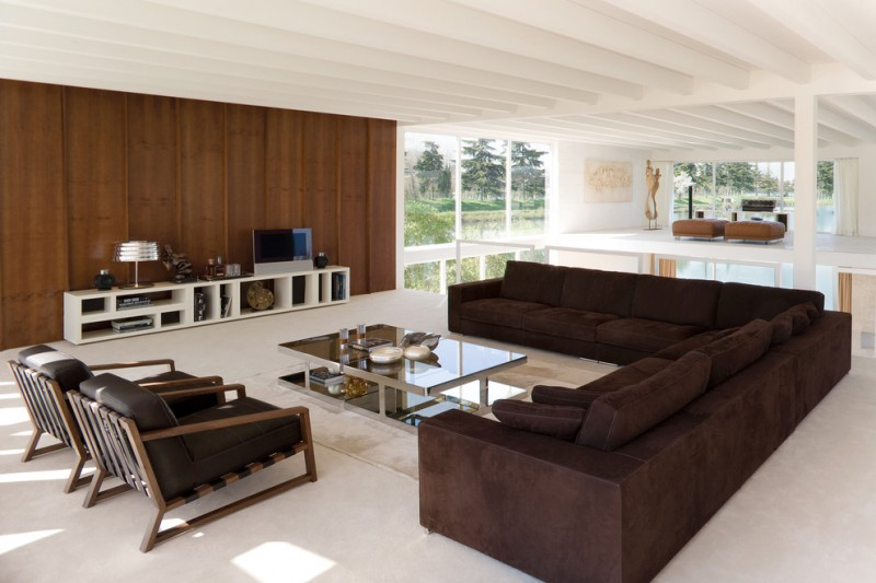 modern living room with brown sectional sofa chairs carpet table shelves
