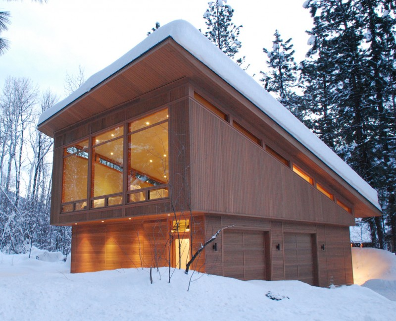 modern vacation home exterior with shed roof and glass windows wooden deck walls and doors