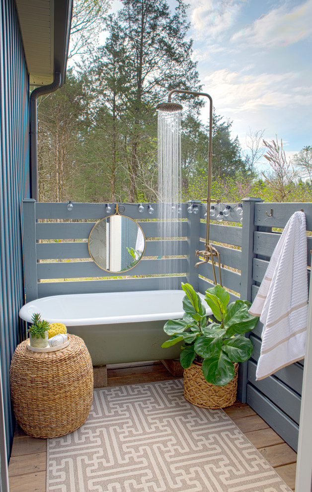 outdoor bathroom with white tub, shower head, rattan ottoman, rattan pot, brown rug, grey wooden fence, mirrors on the fence, small buls along the fence
