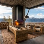 Outdoor Corner Fireplace Hanging Lamp With Silver Shade Log Framed Sofa Deck Wooden Floor And Ceiling Concrete Floor