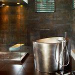 Oval Stainless Steel Japanese Soaking Tub Brown Tiles Floors And Walls Wooden Cabinet Granite Countertop Glass Door Shower Room
