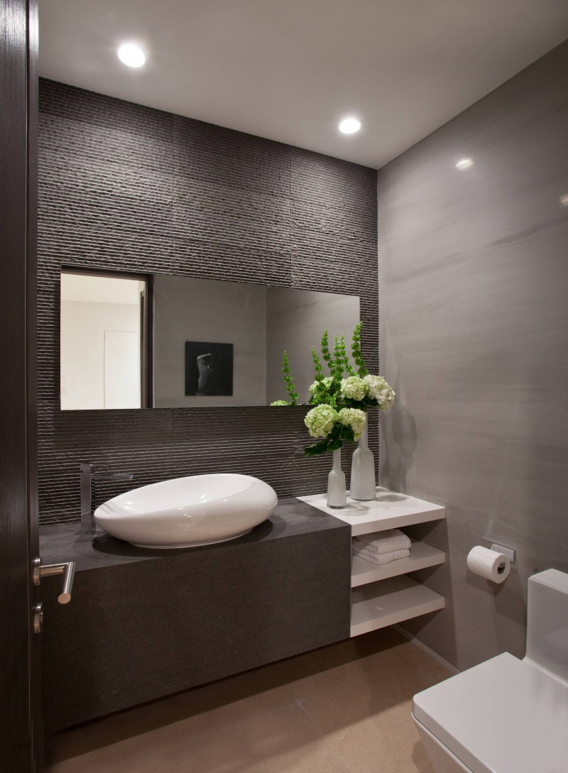 oval vessel sink textured wall floating vanity flower arrangement wall mirror toilet paper holder recessed lights