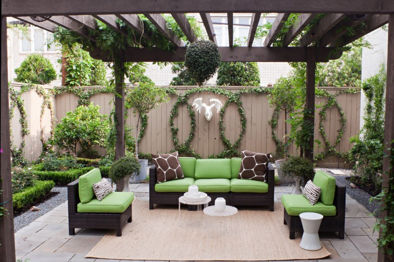 patio under a pergola with rattan rug, dark rattan chair with green cushion, white round coffee table, plants on circle hanging on the fence, stag deer head decor
