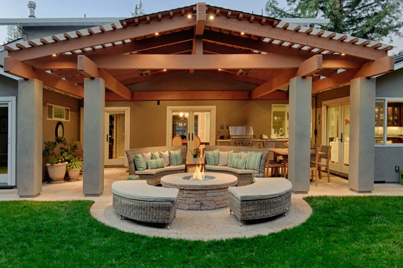 patio with dark toned wood pergola supported with concrete pillars oversized beams round shaped cushion with accent pillows round fire table for patio