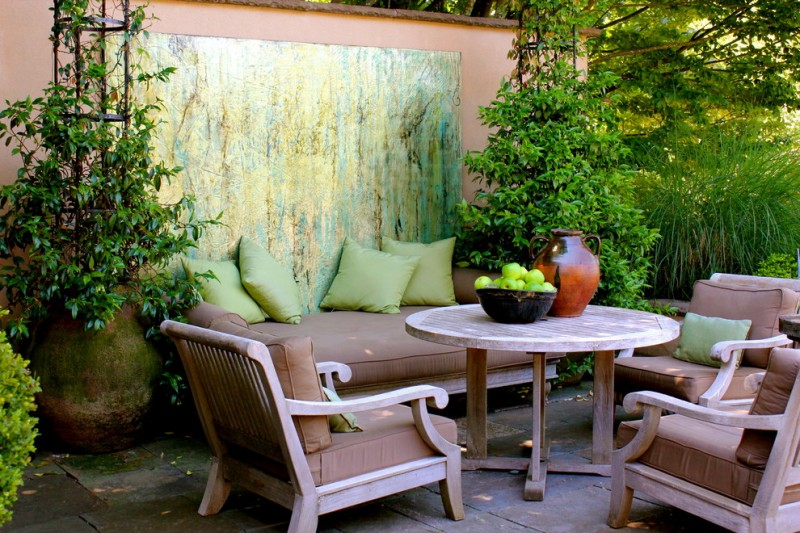 patio with wooden chair with brown cushion, wooden round table, plants in big pots, green paintings on the wall