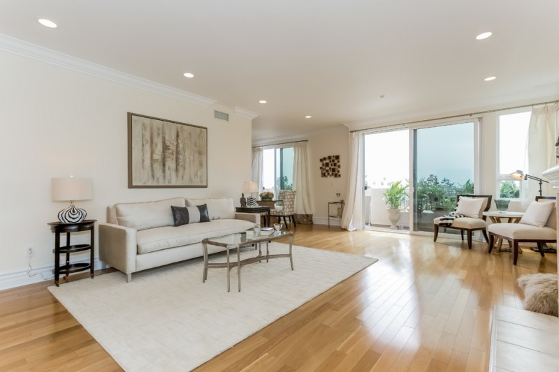 penthouse in los angeles beautiful floor ceiling lights windows curtains carpet sofa tables chairs lamps pillows transitional living room