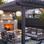 Pergola With Wooden Chairs With Grey Cushion, Grey Coffee Table, Fireplace, Globe Lights
