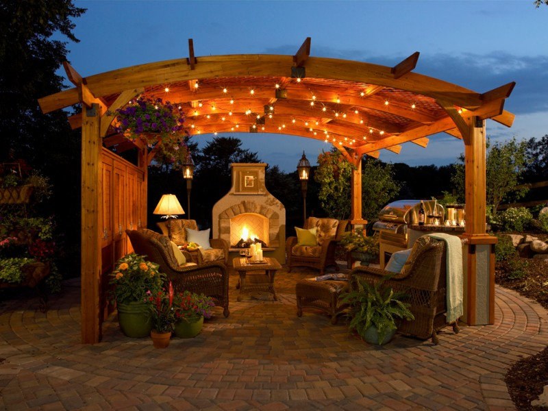 pergolla with light strands on the roof, floor lamp on both ends of fireplace that face set of comfortable rattan chairs with brown cushion
