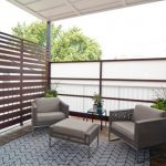 Private Balcony With High Horizontal Wooden Fences, Opaque Screens, Grey Set Chairs And Ottoman For Coffee Table, Glass Side Table, Carpet, Plants