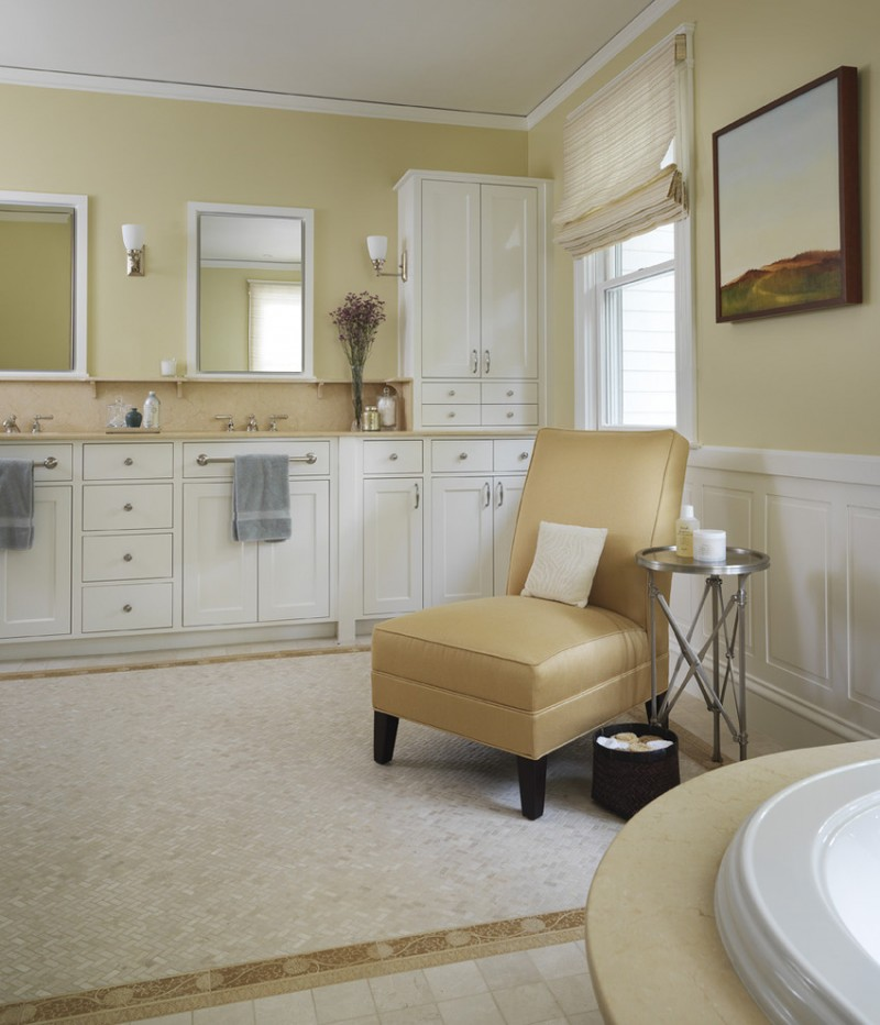 rest room with brown sink, white cabinet with towel bar, white sconces, long vertical mirror, brown chair, silver small round side table
