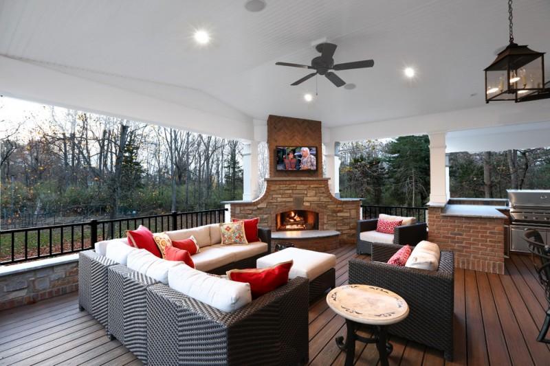 sectional sofa corner fireplace brick pavers wall mount TV ceiling hanging lamp medium toned deck wooden floor