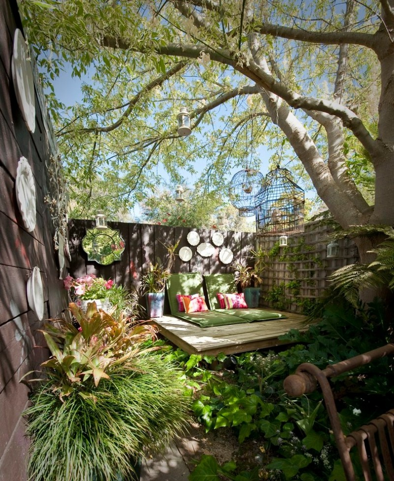 shabby garden with deck with green cushion, pink pillow, ornamental white plates and mirrors on the fence, plants, bird cages