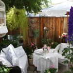 Shabby Patio With White Linen Covered Rattan Chairs, White Crochet Covered Table, Colorful Flower Plants, Decor On Fence, White Bird Post, White Bird Cage