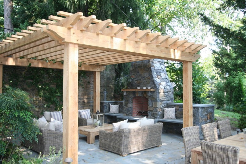simple backyard patio with oak pergola without canopy rattan made outdoor furniture wooden center table stone fireplace concrete tiles floors