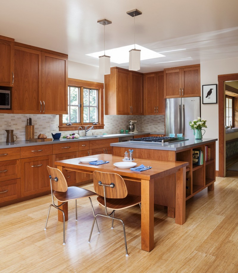 simple & minimalist kitchen designed in mission style wooden cabinets wooden dining furniture white tiles backsplash grey & gloss top kitchen island stainless steel appliances lighter toned wooden floors
