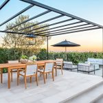 Simple & Minimalist Metal Pergola In Black Black Stained Metal Pendant Lamp With Glass Shading Puffed Chairs And Wood Table Concrete Slabs Floors