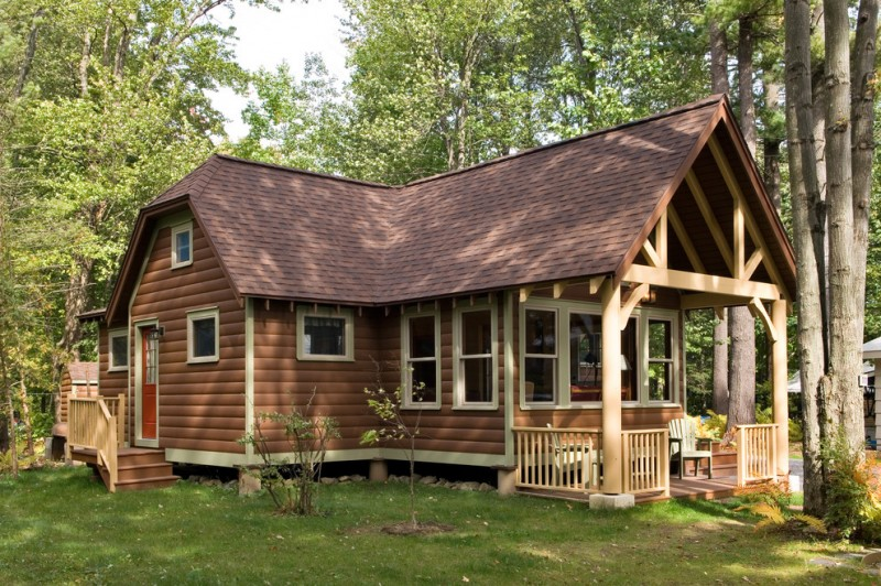 small cabin with square wooden beam front porch wooden deck wall log poles red wooden door with glass